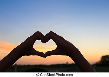 Female hands in the form of heart against sunlight in sunset sky,