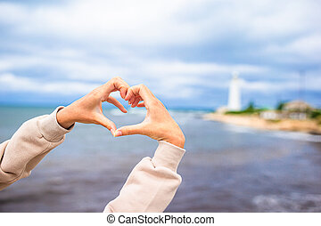 Female hands in the form of heart against the lighthouse