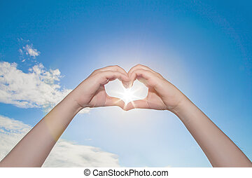 Female hands in the form of heart hold the sun in center against the sky in the afternoon., Hands in shape of love heart., Make hay while the sun shines.