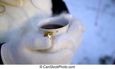 Female hands in white mittens holding steaming white cup of...