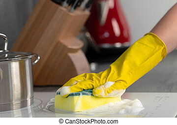 Female hands in yellow gloves cleaning electrical stove with a sponge close up