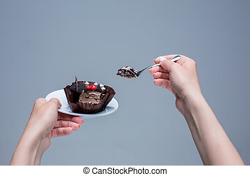 Female hands keeping cake with spoon on gray