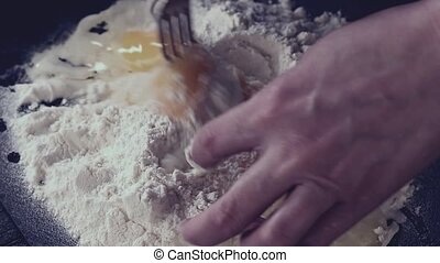 Female hands knead eggs in flour for making dough over black...