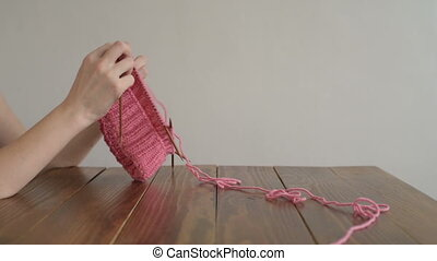 Female hands knitting a pink hat