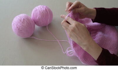 Female hands knitting a pink sweater