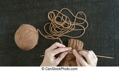 Female hands knitting a sock on a black shabby background.