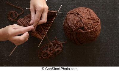 Female hands knitting on black back
