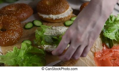 Female hands make a sandwich with a fresh homemade bagel and smoked salmon