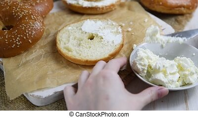 Female hands make a sandwich with a fresh homemade bagel with low fat cream cheese.