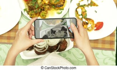 Female hands make photo on a smartphone in a restaurant with...