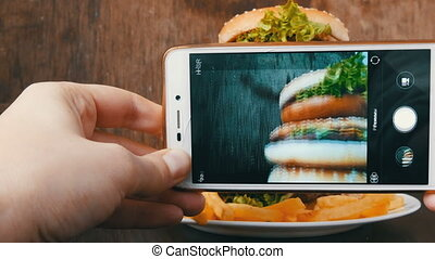 Female hands make smartphone photo of a large burger on a...