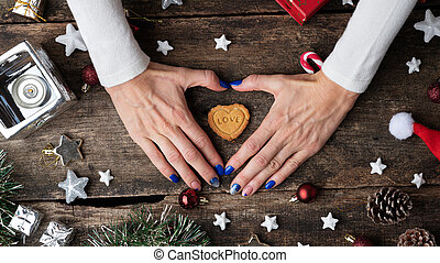 Female hands making a heart shape around a holiday cookie placed in the middle of christmas setting