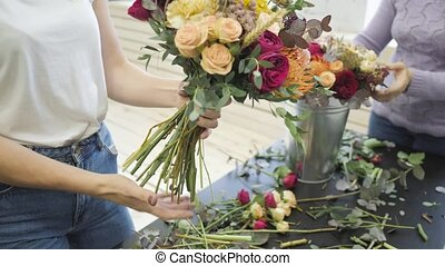 Female hands making beautiful flower composition in floral shop