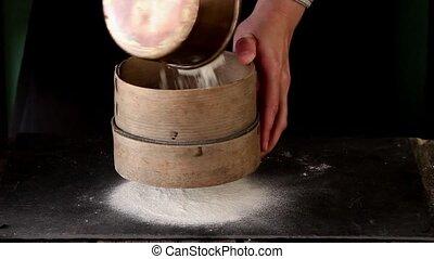 Female hands making dough for pasta over black table