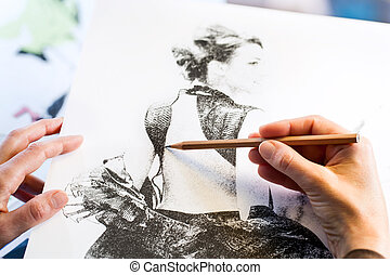 Female hands making fashion sketch.
