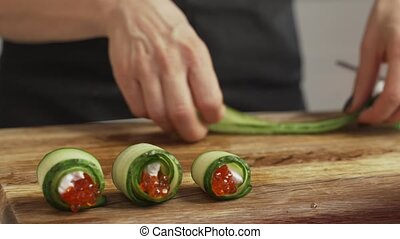 Female hands making snack roll of caviar cheese and cucumber