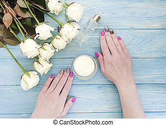 female hands, manicure, cosmetic cream, rose flower on wooden background