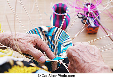 Female hands manually weaving bamboo basket