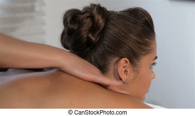 Female hands massages woman's neck