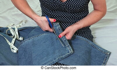 Female hands of a seamstress cutting fabric with a scissors