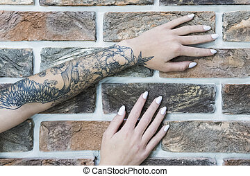 Female hands on a brick wall