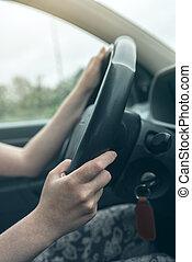 Female hands on car steering wheel
