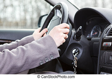 Female hands on steering wheel in land vehicle