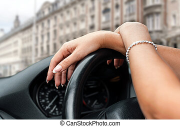 Female hands on steering wheel of a car