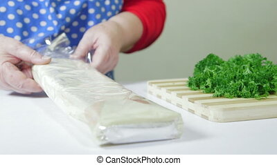 bake frozen puff pastry sheets - Female hands open package...