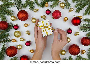 female hands opens a small gift box on white background with golden and red christmas balls and fir branches. Winter flat lay. Christmas composition.