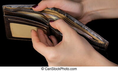 Female hands out cash dollars from purse. Dollar and...