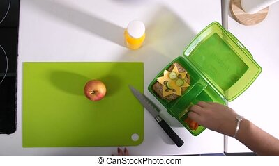 Female hands packing food in school lunchbox