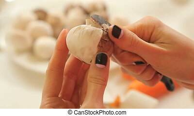 Female hands peeling champignons in the kitchen