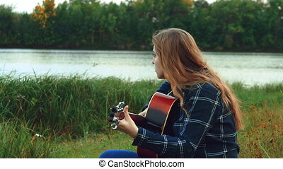 female hands play the guitar. A happy carefree young girl plays the guitar while she is in the woods all alone, when the sun begins to set.