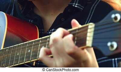 female hands play the guitar. A happy carefree young girl...