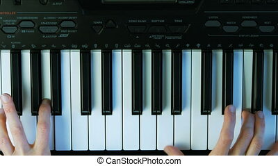 Female hands playing piano. A woman touches the keys with her fingers.