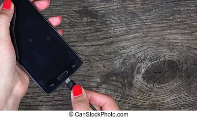 female hands plug smart phones to charger wires
