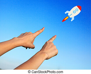 Female hands point to the rocket