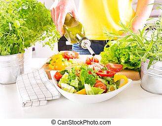 female hands pouring oil from bottle into the bowl of salad