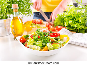 Female hands preparing vegetable salad in the kitchen