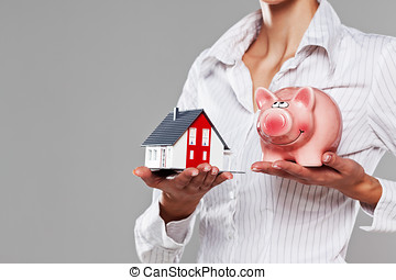 Female hands presenting a piggy bank and a model house...