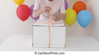 Female hands pulling a red ribbon to open gift box in a blue...