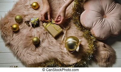 Female hands put a gift box on a fur skin. Tinsel and golden Christmas balls are spread around. Preparing for Happy Winter Holidays. Festive mood. Merry christmas and new year. Close up. Slow motion