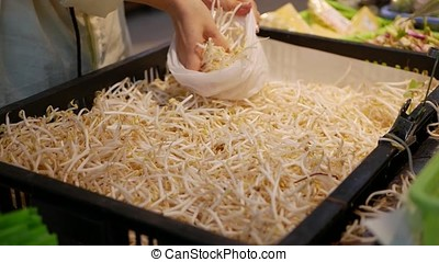 Female hands puts soybean sprouts in a package in a store....