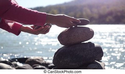 Female hands putting pebble stack next to the mountain river in slow motion.