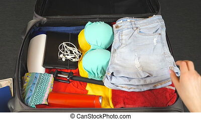 Female hands putting summer things in a suitcase. Arms of young woman packing bag with personal stuff for trip or vacation. Girl gets ready for flight to resort. Concept of travel. Top view Close up