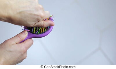 Female hands remove lost hair from a comb with multi-colored...
