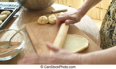 Female hands roll the dough with a rolling pin, sprinkle with cinnamon roll and put on a tray to bake