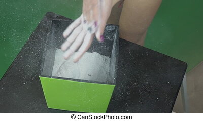 Female hands rub on skin white sport magnesia from square container.