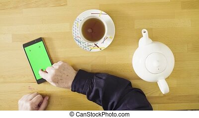 Female hands scrolling a tablet with green screen - Top...
